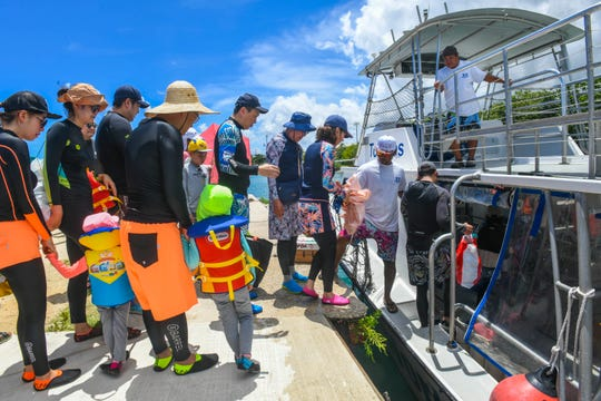 Deckhand Daiwin Igular assists passengers as they board Real World Diving's vessel, Toninos, at the Gregorio D. Perez Marina in Hagåtña July 26. Guam welcomed 123,258 visitors in June, a decrease of 2.3% compared to June 2018.