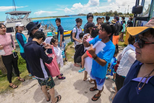 Scuba Company tour guide Hiroyuki Niitsuma, center, organizes passengers preparing to leave on waiting tour buses and those waiting to board two company boats at the Gregorio D. Perez Marina in Hagåtña in this July 26, 2019, file photo.