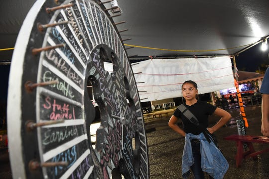 Robin Cruz watches the wheel spin during a game at the Liberation carnival in Hagåtña on July 26, 2019.