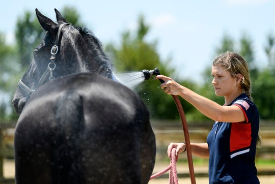 Callie Jones helps Phil, her 11-year-old Hanoverian horse, cool off following a conditioning practice with Trainer Angela Jackson, not pictured, at Jackson's training facility in Henderson, Ky., Thursday afternoon, July 25, 2019. Jones and Phil work on dressage training about five days a week to stay limber for upcoming competitions.