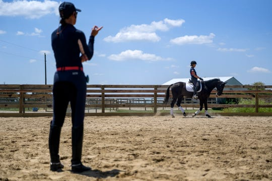 Trainer Angela Jackson, front left, gives instructions to Callie Jones and Phil, her 11-year-old Hanoverian horse, during a conditioning practice at Jackson's training facility in Henderson, Ky., Thursday afternoon, July 25, 2019. Jones and Phil work on dressage training about five days a week to stay limber for upcoming competitions. Jones, currently a 21-year-old student at Murray State University, started training with with Jackson when she was 14.