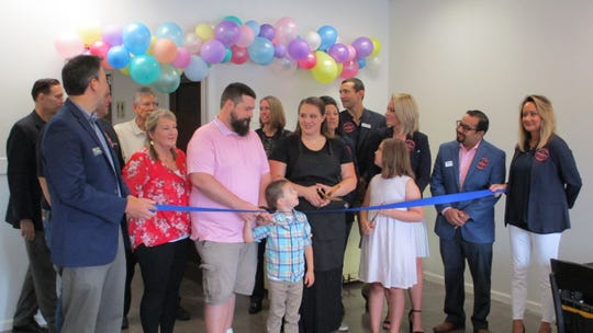 Owner Kaitlyn Wright gathers in her new business, Butter Custom Bakery, with friends and family for a ribbon cutting.