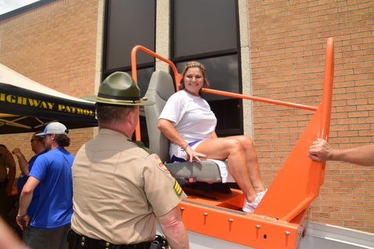 "Tennessee Highway Patrol Trooper Sgt. Randall Martin gets Kellie Howell settled in the ""Seatbelt Convincer."" July 20, 2019."