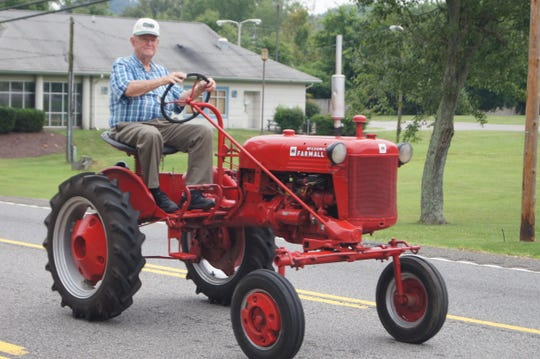 Henry Lenoir putters down the parade route on his 1955 Farmall Cub tractor at the 66th annual Karns Community Parade on Saturday, July 20, 2019.