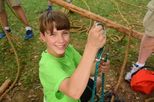 Brendan Puhr, 12, from Boy Scout Troop 50 rigs up the rope bridge at the 66th annual Karns Community Fair. July 20, 2019.