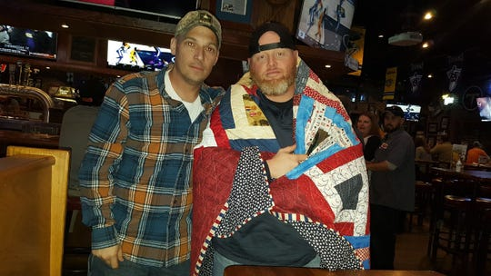 Andrew Lee stands with a good friend of his, Jason Gresham, after Quilts of Valor awarded him with a quilt.