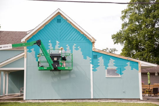 Sandra Fettingis works on her mural on the side of 701 Wabash ave, Friday, July 26, 2019 in Lafayette. Over ten artists will continue to work until Friday, Aug. 2.