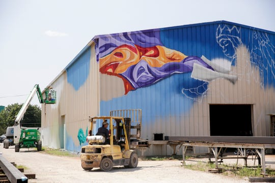 Sophi Odling works on her mural on the side of Indiana Steel Fabricating, Thursday, July 25, 2019 in Lafayette. Over ten artists will continue to work until Friday, Aug. 2.