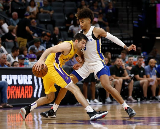 Golden State Warriors guard Jordan Poole, right, blocks the drive of Los Angeles Lakers guard Dakota Mathias during the second half of an NBA basketball summer league game in Sacramento, Calif., Tuesday, July 2, 2019.