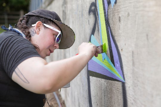 Alyse Chinnock works on her mural at the Community Garden on Smith st., Friday, July 26, 2019 in Lafayette. Over ten artists will continue to work until Friday, Aug. 2.