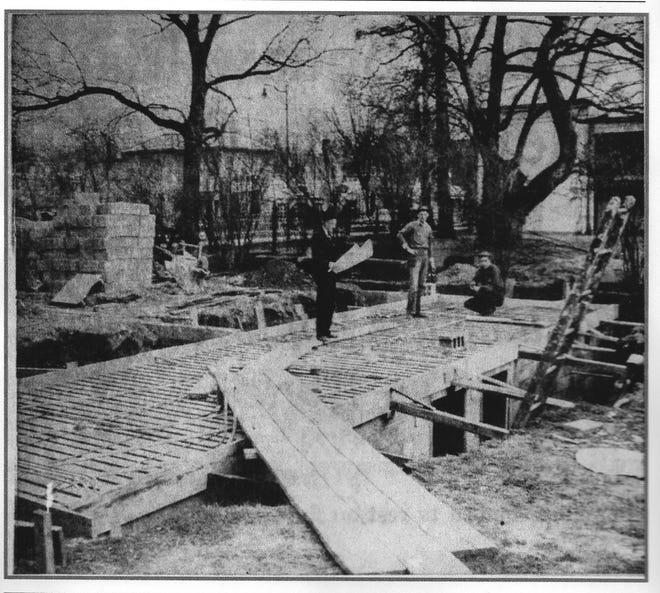 This photo shows 333/335 N. Columbus St. under construction in 1950. Contractor A. B. Van Gundy is standing in the center studying the blue prints for the building. To the right/south is the Tallmadge/Mithoff/Alfred house that stood at 321 N. Columbus. Photo from the E-G June 3, 1950, p.E-6.