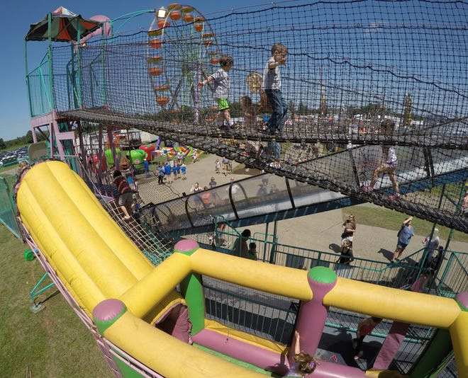 Children navigate the Riders attraction, one of many provided by Skerbeck Entertainment at the Fowlerville Family Fair Wednesday, July 24, 2019.