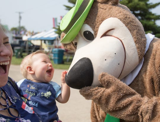 ShyLinn Sporer, left, laughs as she holds her nephew 7 1/2-month-old Sebastian Sporer, thrilled to meet Yogi Bear at the Fowlerville Family Fair Thursday, July 25, 2019.