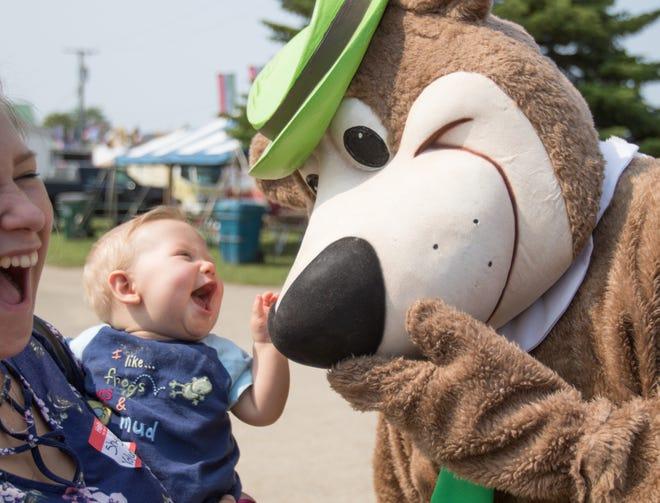ShyLinn Sporer, left, laughs as she holds her nephew 7 1/2-month-old Sebastian Sporer, thrilled to meet Yogi Bear at the Fowlerville Family Fair Thursday, July 25, 2019.