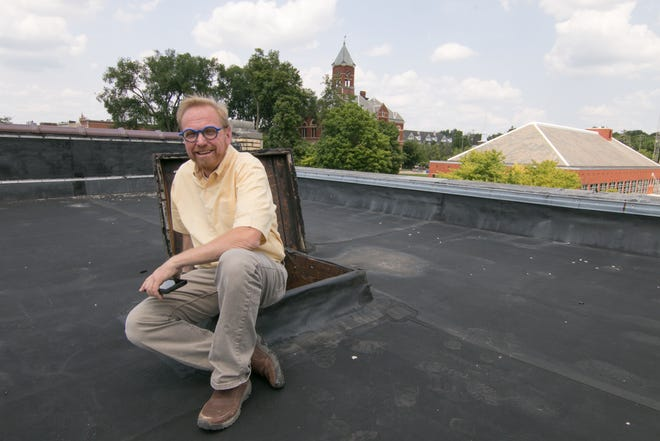 Jeff Doyle sits at the rooftop hatch of The Pearl building in downtown Howell Friday, July 26, 2019, where he plans to build apartments and a commercial space that could be a restaurant or retail space.