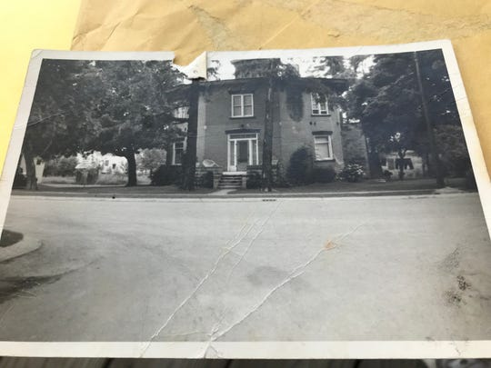 A black and white photo of Dansville's octagon house on East Mason Street, shows a small stone porch, big enough for a few chairs, that once led up to its front door.