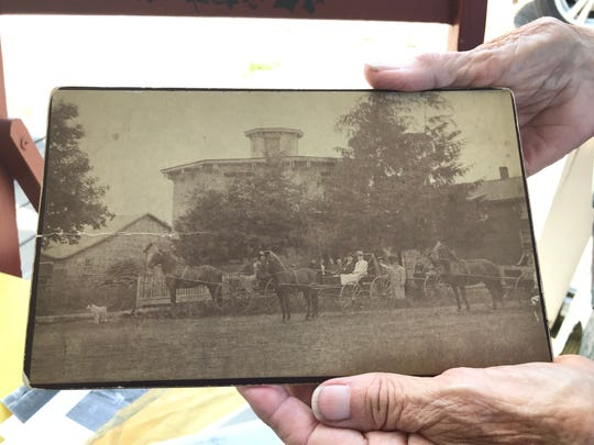 Owner Diane Swan holds an aging photo of Dansville's octagon house taken at least a century ago.
