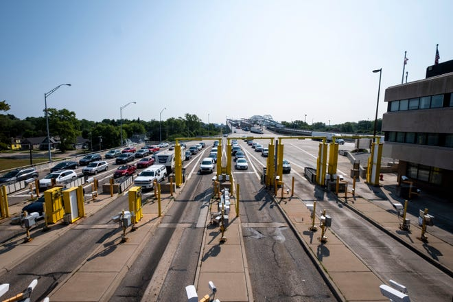 Vehicles entering the United States from Canada wait to drive through radiation detectors to enter que lines Friday, July 26, 2019, on the Blue Water Bridge in Port Huron.