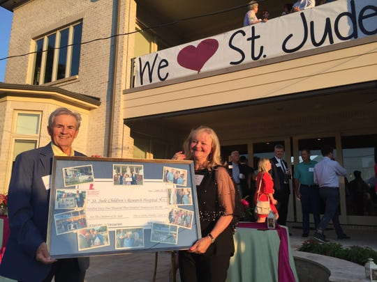 Dan and Shirley Mullally hold up a commemorative plaque and check given to them by St. Jude to signify how much money their annual party raised for the hospital.