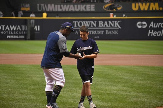 Oconomowoc's Nathaniel Froemming (right), who lost his right arm in a car crash, threw out the first pitch at a Brewers game in June.