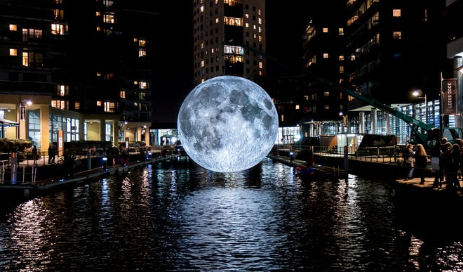 Museum of the Moon, a 23-foot inflatable moon made with NASA images, hangs over the water at Leeds Dock in England. The artwork is coming to Milwaukee Aug. 9.