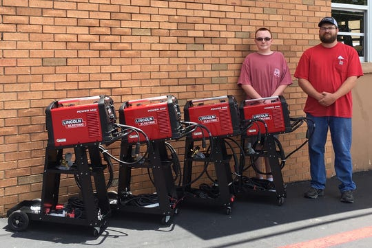 Flippin FFA Vice President Railey Parnell (from left)and Flippin FFA Instructor Talon Vancuren are pictured with four new Lincoln welding machines. The school was able tp add the equipment to it's agriculture program though a Carl D. Perkins grant.