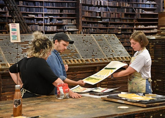 Amber Richards and Devin Goebel inspect a poster produced by intern Rosa Jeffiers at Hatch Show Print on July 23, 2019.
