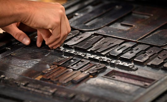 Letterpress printmakers manually insert metal type onto the press to make a poster July 23, 2019, at Hatch Show Print.