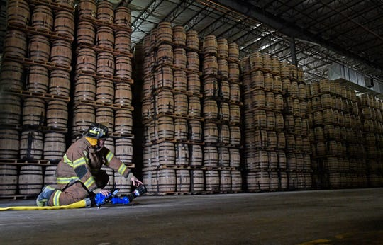 A firefighter sets up a hose and nozzle inside a barrelhouse during a Jack Daniel's Volunteer Fire Brigade training exercise on Monday, July 22, 2019, in Lynchburg, Tenn.