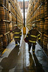 Caleb Barnett and Cody Cashion familiarize themselves with a barrelhouse during a Jack Daniel's Volunteer Fire Brigade training exercise Monday, July 22, 2019, in Lynchburg, Tenn.