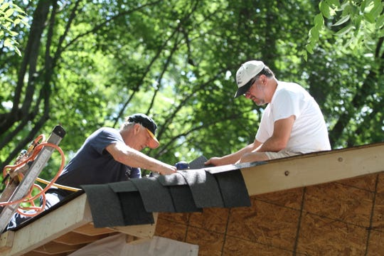 Volunteers work on the roof of the Woodland Street project known as Christmas in July on Tuesday, July 23, 2019.