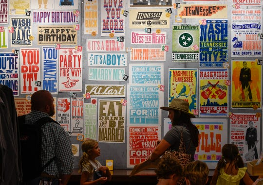 Visitors look at posters for sale at Hatch Show Print inside the Country Music Hall of Fame and Museum in Nashville on July 23, 2019.