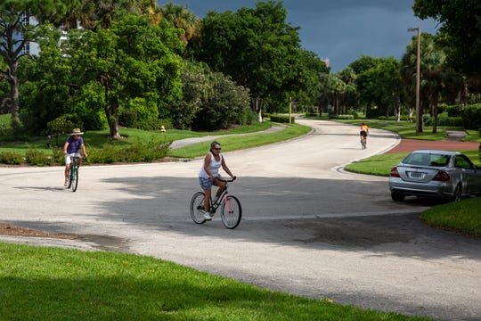 Biker riders make their way south into a parking lot to navigate a gap in a bike path that dead-ends at the end of Crayton Road north of Seagate Drive, Thursday, July 25, 2019, in North Naples. At far right, Nancy Koeper, a Vanderbilt Beach resident moves north on Crayton Road after crossing through the parking lot.