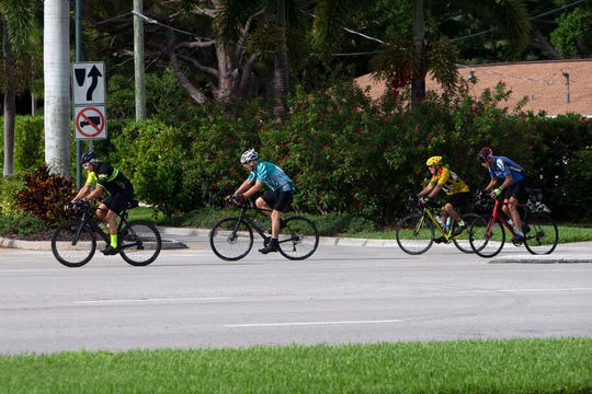 Bikers make their way past Crayton Road as they head east on Seagate Drive on Thursday, July 25, 2019, in Naples
