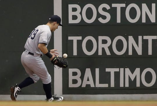 New York Yankees left fielder Mike Tauchman plays a double off the wall by Boston Red Sox's Jackie Bradley Jr. in the third inning of a baseball game at Fenway Park, Thursday, July 25, 2019, in Boston. (AP Photo/Elise Amendola)