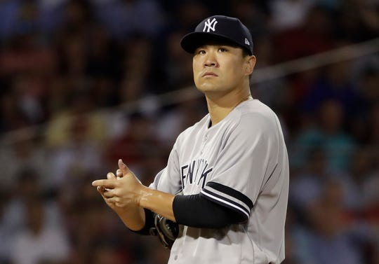 New York Yankees starting pitcher Masahiro Tanaka rubs the ball as he is taken out in the fourth inning of a baseball game against the Boston Red Sox at Fenway Park, Thursday, July 25, 2019, in Boston. (AP Photo/Elise Amendola)