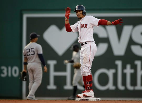 Boston Red Sox's Mookie Betts celebrates after hitting a two-run double as New York Yankees second baseman Gleyber Torres (25) looks to the outfield in the first inning of a baseball game at Fenway Park, Thursday, July 25, 2019, in Boston. (AP Photo/Elise Amendola)