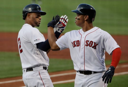 Boston Red Sox's Xander Bogaerts, left, celebrates his three-run homer with teammate Rafael Devers in the first inning of a baseball game against the New York Yankees at Fenway Park, Thursday, July 25, 2019, in Boston. (AP Photo/Elise Amendola)