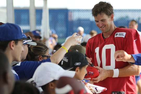 Eli Manning signs autographs for fans after practice, Thursday, July 25, 2019.