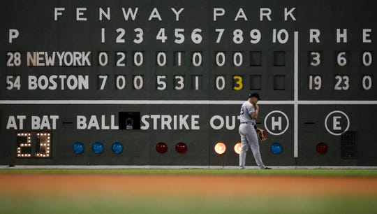 New York Yankees left fielder Mike Tauchman walks back to his position with the scoreboard showing the Boston Red Sox ahead 19-3 in the eighth inning of a baseball game at Fenway Park, Thursday, July 25, 2019, in Boston. (AP Photo/Elise Amendola)