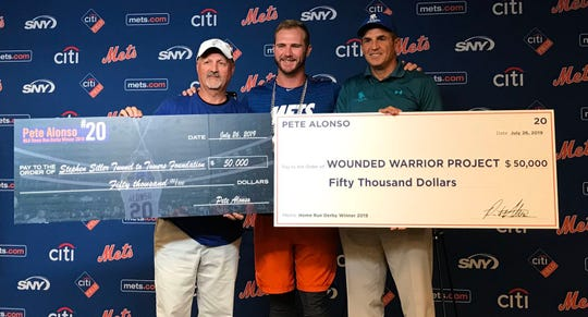 Mets first baseman Pete Alonso, center, presenting checks to the the Stephen Siller Tunnel to Towers Foundation and the Wounded Warrior Project on Friday, July 26, 2019 before New York hosted the Pirates. Alonso's donation came from the prize money he won at MLB's Home Run Derby on July 8.