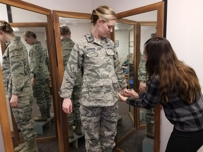 Stacey Butler, right, a clothing designer with the Air Force Life Cycle Management Center's Air Force Uniform Office, measures Capt. Taylor Harrison's maternity Airman Battle Uniform. The new uniforms were designed and developed by the office and are available to pregnant Airmen around the world.