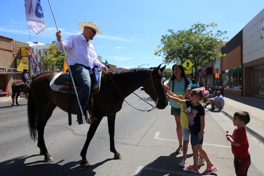 Dale Hooper allows a family to pet his horse, Thursday, July 25, 2019, during the Connie Mack parade in Farmington.