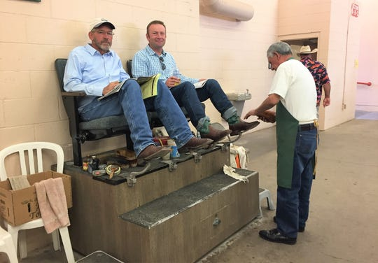 Two men from Texas get their boots shined and polished the old fashioned way.