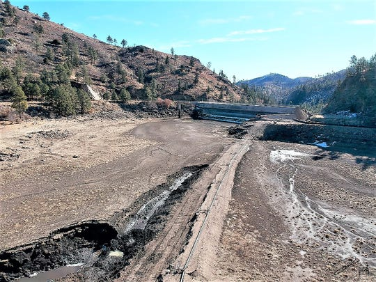 The lake bottom is exposed, but the digging (foreground left) is revealing decades of accumulation before the Little Bear Fire in 2012. The dam is visible at the back.