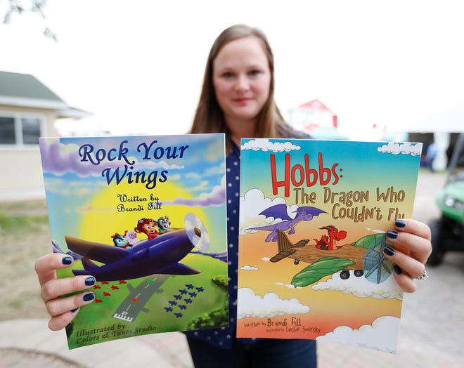 Brandi Fill of Hadley, Massachusetts holds up her two aviation-themed children's books that are for sale in the EAA Warehouse on the EAA grounds.