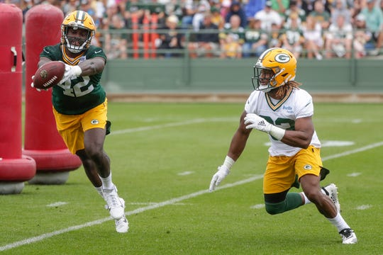 Linebacker Oren Burks (42) catches a tipped pass intended for running back Aaron Jones (33) during Green Bay Packers training camp at Ray Nitschke Field Friday, July 26, 2019, in Green Bay, Wis.