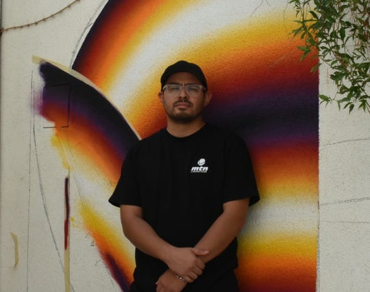 Chris Sanchez poses in front of his mural at Ace Hotel & Swim Club in Palm Springs on July 25, 2019.
