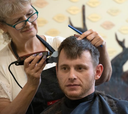Tammy Abrams gives Brandon Stafford a free haircut during the 70th anniversary celebration at the Waterfront Rescue Mission on Friday.