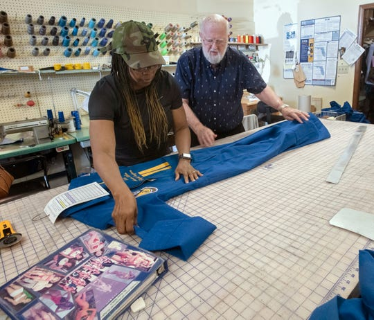 Candy Whitehurst and Sam Miller inspect a flight suit the pair created for one of the new members of the Blue Angels on Thursday. Miller, 81, has made hundreds of flights suits for the Blue Angels at his Pensacola shop, now called Jellie B The Sewing Box.